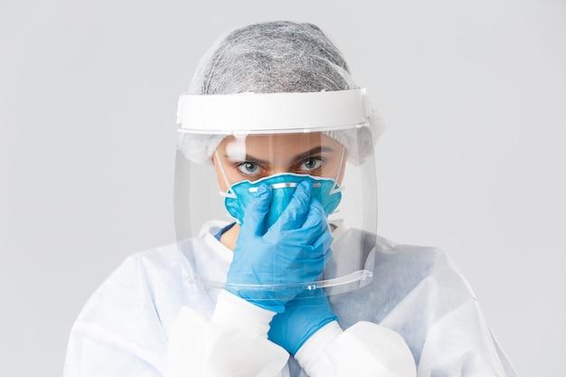 Covid-19、ウイルス、健康、医療従事者、検疫の概念を防ぎます。クローズアップの深刻な女性医師、個人用保護具の看護師、人工呼吸器を装着し、カメラを決定