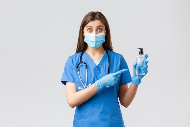 Covid-19、ウイルス、健康、医療従事者、検疫の概念を防ぎます。青いスクラブ、医療用マスク、手袋をはめた熱狂的な女性看護師または医師が、手指消毒剤を指差して、驚いたように見えます