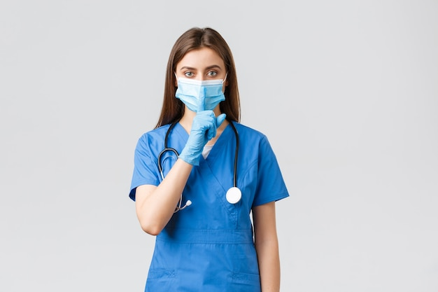 Covid-19、ウイルス、健康、医療従事者、検疫の概念を防ぎます。声を抑えてください。青いスクラブ、医療用マスクと手袋、身をかがめる、唇に指を押す真面目な女性看護師