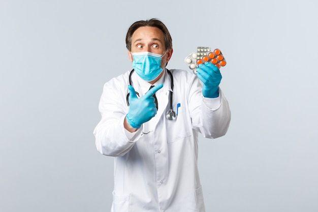 Covid-19, профилактика вируса, медицинские работники и концепция вакцинации. взволнованный врач в медицинской маске и перчатках указывает пальцем на лекарство, показывает лекарства, рекомендует таблетки