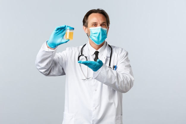 Covid-19, 바이러스, 의료 종사자 및 예방 접종 개념을 예방합니다. 의료용 마스크와 장갑을 끼고 웃는 의사는 깨끗한 테스트 결과에 만족하고 흰색 배경에 소변 샘플을 보여줍니다.