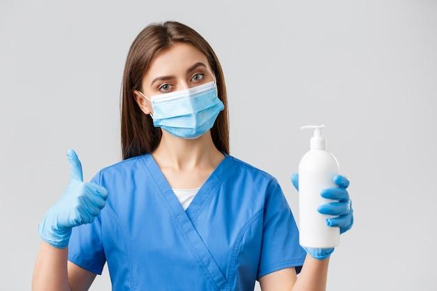 Covid-19, профилактика вируса, концепция медицинских работников. серьезная медсестра или врач в синих скрабах, медицинской маске и перчатках рекомендуют использовать мыло или дезинфицирующее средство против коронавирусной инфекции.