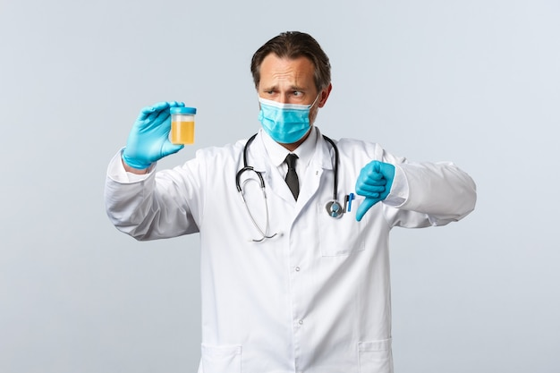 Covid-19, preventing virus, healthcare workers and vaccination concept. disappointed doctor in medical mask and gloves show urine sample, thumbs-down have bad test result, white background