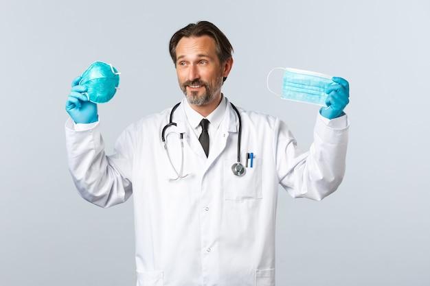 Covid-19, prevenzione del virus, operatori sanitari e concetto di vaccinazione. il medico soddisfatto in guanti e camice bianco che mostra respiratore medico e maschera, spiega l'importanza di indossare i dpi durante il coronavirus.