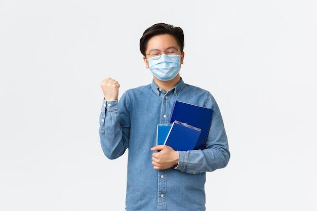 Covid-19, prevenzione del virus e distanza sociale al concetto universitario. rallegrandosi, studente asiatico soddisfatto ha superato gli esami, indossa una maschera medica, porta quaderni e pompa a pugno, vincendo o trionfando.