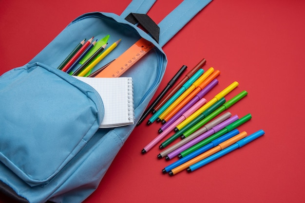 Профилактика covid-19 при возвращении в школу и новая нормальная концепция. вид сверху на рюкзак со школьными принадлежностями на красном фоне.
