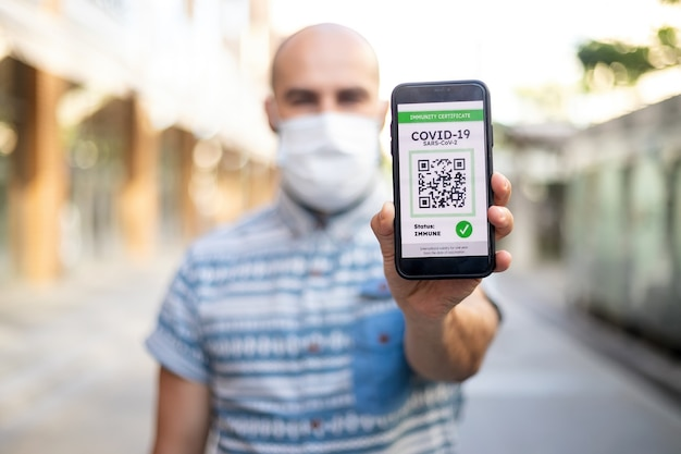 Covid-19 protection concept. happy young man holding mobile phone with digital international health passport application, confirming vaccination, ready for travel Premium Photo