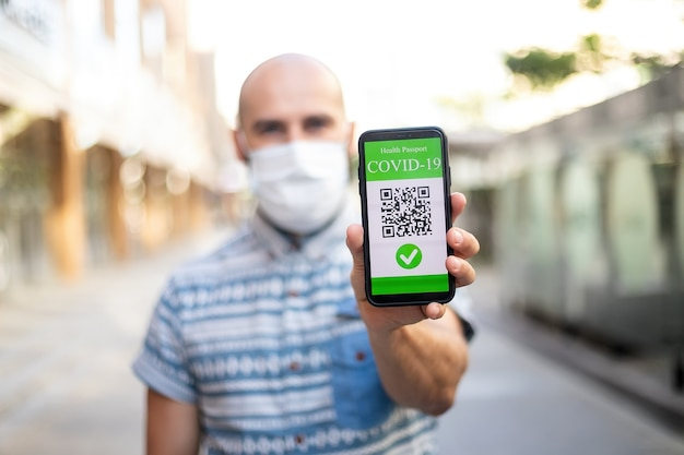 Covid-19 protection concept. happy young man holding mobile phone with digital international health passport application, confirming vaccination, ready for travel
