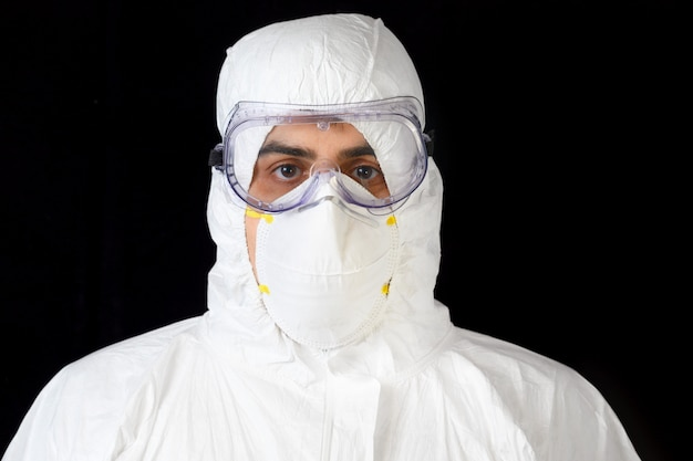 Covid-19 protective equipment. portrait of doctor or male nurse wearing personal protective equipment on black isolated