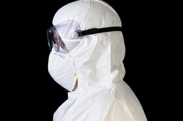 Covid-19 protective equipment. side view portrait of doctor or male nurse wearing personal protective equipment on black isolated