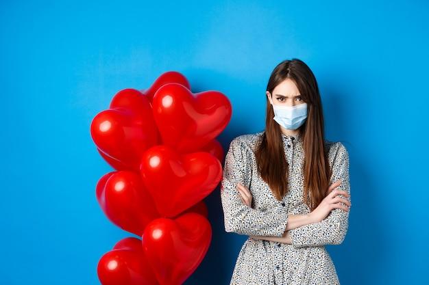 Covid-19、検疫および健康管理。医療マスクの怒っているガールフレンド、バレンタインデーの赤いハートの風船の近くに立って、胸に腕を組んで、気分を害した、青い背景を眉をひそめる