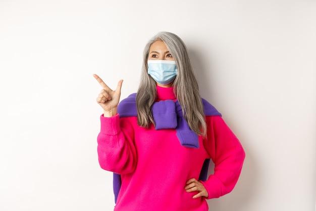 코비드-19, 검역 및 잠금 개념. 얼굴 마스크를 쓴 세련된 아시아 할머니는 왼쪽 상단 모서리를 가리키고 바라보며 로고와 미소, 흰색 배경을 보여줍니다.