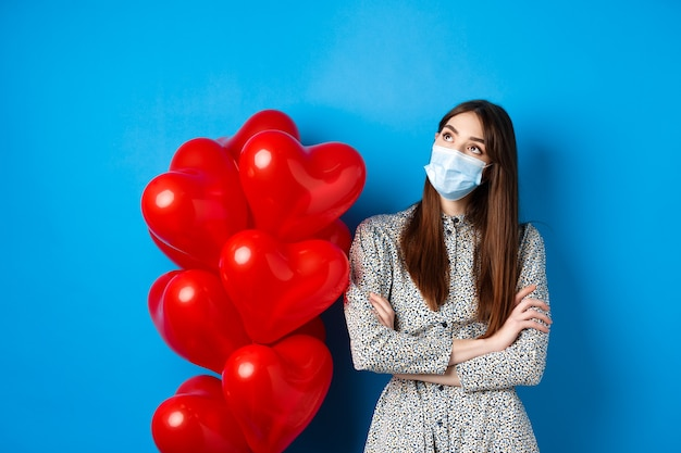 Covid-19, quarantine and health conept. dreamy beautiful girl in face mask and dress, looking at upper left corner pensive, standing near valentines day balloons, blue background