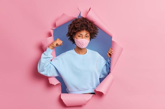 Covid 19 quarantena e concetto di cura della salute. una donna afroamericana sicura di sé alza il braccio e mostra i muscoli