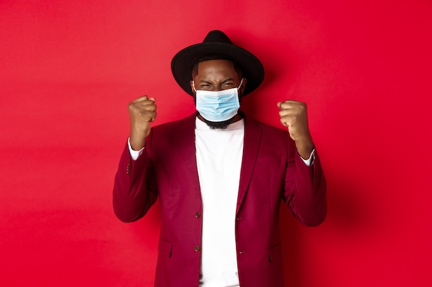 Covid-19, quarantine and holidays concept. cheerful african american man showing clenched fist and rejoicing of winning, achieve goal, wearing medical mask from coronavirus