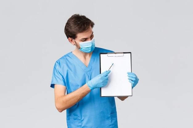 코비드-19, 검역, 병원 및 의료 종사자 개념. 의사는 코로나바이러스로부터 보호하기 위한 조치를 취하는 것이 중요하다고 설명합니다. 클립보드를 가리키는 수술용 마스크와 의료용 마스크를 쓴 의사.