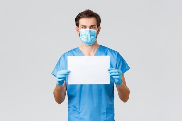 Covid-19, карантин, больницы и концепция медицинских работников. серьезный молодой врач в медицинской маске, скрабах и перчатках, держит бумагу с манифестом или знаком, борется с коронавирусом, просит остаться дома