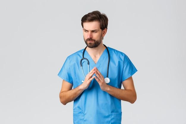코비드-19, 검역, 병원 및 의료 종사자 개념. 어려운 문제를 해결하는 사려 깊은 고민하는 의사, 뾰족한 손가락이 인상을 찌푸리고 시선을 돌리고 문제가 있고 스크럽과 청진기를 착용