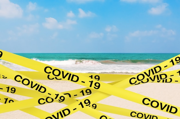 Covid-19 quarantine yellow tape strips enclose zone of the ocean or sea sand beach on a white background. 3d rendering