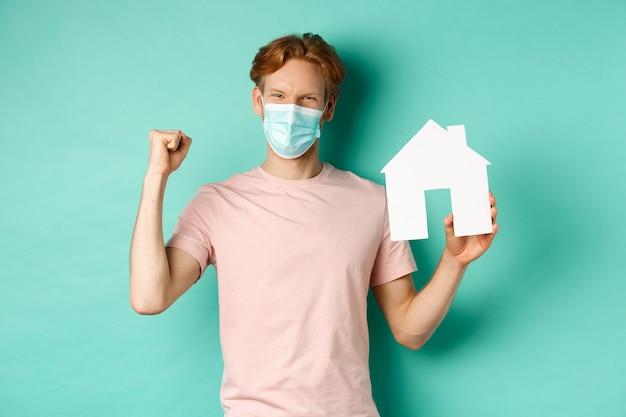 Covid-19 e concetto di bene immobile. felice redhead uomo in maschera medica, mostrando il ritaglio della casa di carta e la pompa del pugno, gioendo e vincendo, in piedi su sfondo turchese.