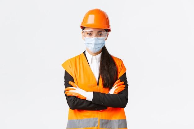 エンタープライズ、建設、ウイルス予防の概念におけるcovid-19安全プロトコル。労働者がコロナウイルスの間にプロトコルに従う方法を見て、フェイスマスクを着用して自信を持ってアジアの女性チーフエンジニア
