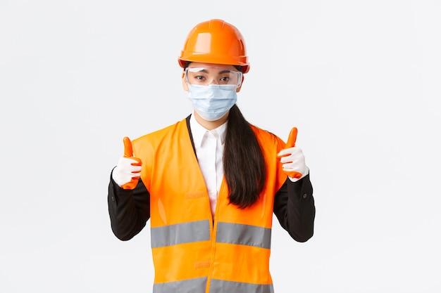 エンタープライズ、建設、ウイルス予防の概念におけるcovid-19安全プロトコル。自信を持って女性のアジアの産業労働者、フェイスマスクとヘルメットのエンジニアが親指を立てて、すべて良い