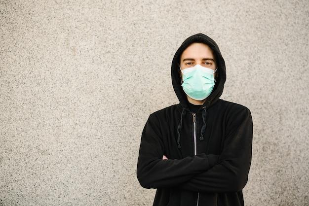 Коронавируса. молодой человек в защитной маске для защиты от болезни covid-19. против sars-cov-2. pandemic. эпидемия. берегите свое здоровье. концепция карантина.