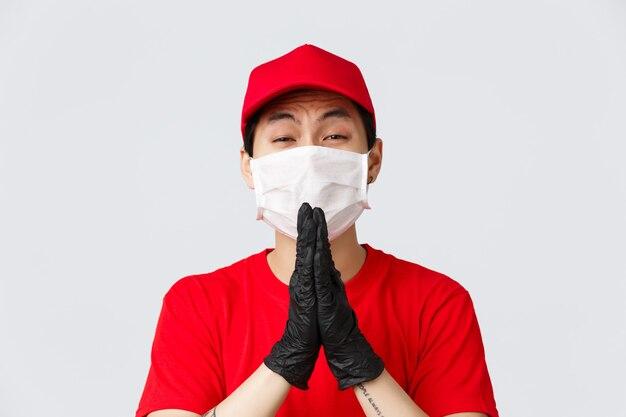 Covid-19、自己検疫のオンラインショッピングと配達のコンセプト。医療用マスクと手袋のしがみつくアジアの宅配便、物乞い、物乞い、助けが必要、灰色の背景に立っている