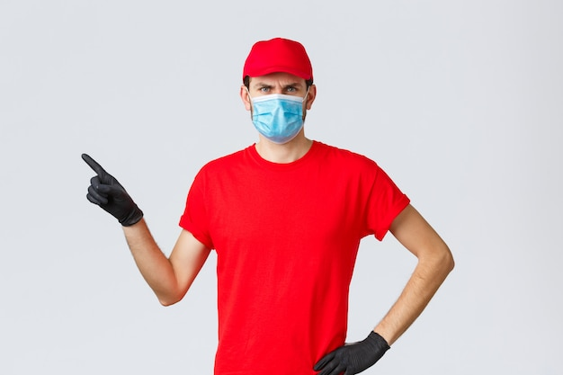 Covid-19、自己検疫、オンラインショッピング、配送のコンセプト。不快な怒っている配達人が宅配便を転がし、眉をひそめ、指を左に向け、医療用マスクを着用する