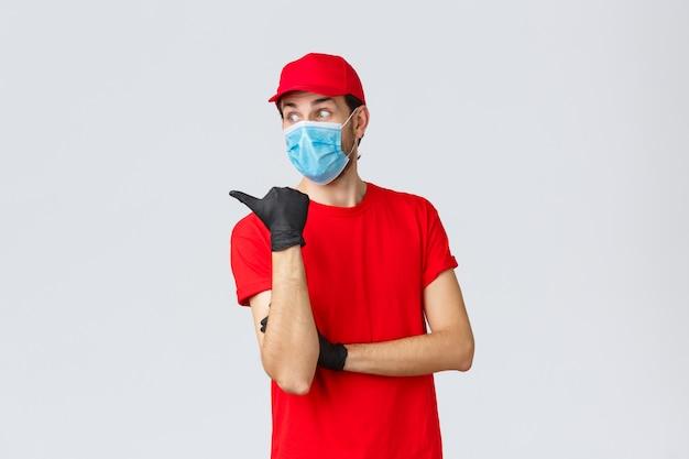 Covid-19、自己検疫、オンラインショッピング、配送のコンセプト。赤い制服を着た驚いた宅配便、フェイスマスクと手袋、親指を向け、印象に残った表情、好奇心を持ってプロモーションを読んで、道を示す
