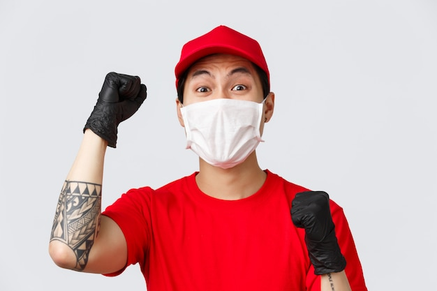 Covid-19, self-quarantine online shopping, delivery concept. close-up of happy chanting courier in red cap and t-shirt, wear medical mask with gloves, raise hands up supportive, encourage or say yes