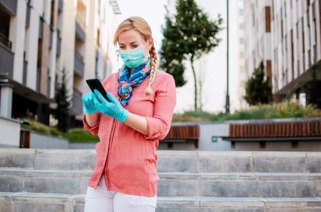 Женщина носит защитную медицинскую одежду, используя мобильный телефон, прогуливаясь по улице города во время вируса covid-19. ответственное поведение при пандемии короны. женщина отправляет sms-сообщения на телефоне с латексными перчатками