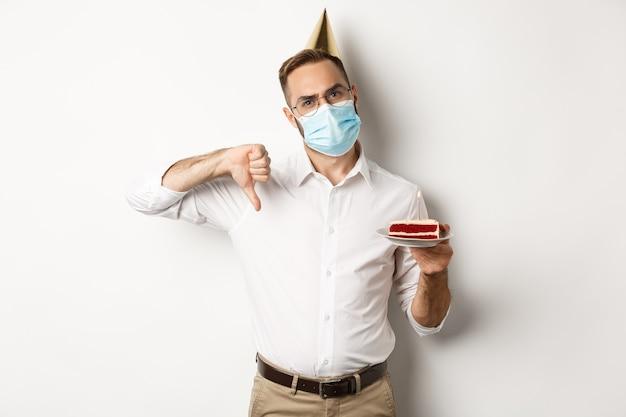 Covid-19, 사회적 거리두기 및 축하. 얼굴 마스크를 쓰고 소원 촛불로 bday 케이크를 들고 엄지 손가락을 내리고 싫어하는 것을 표현하는 실망한 생일 남자