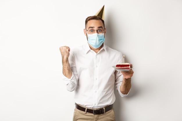 Covid-19、社会的距離とお祝い。フェイスマスクで、bdayケーキを保持し、白い背景に立って喜んで、希望に満ちたお誕生日おめでとう男。