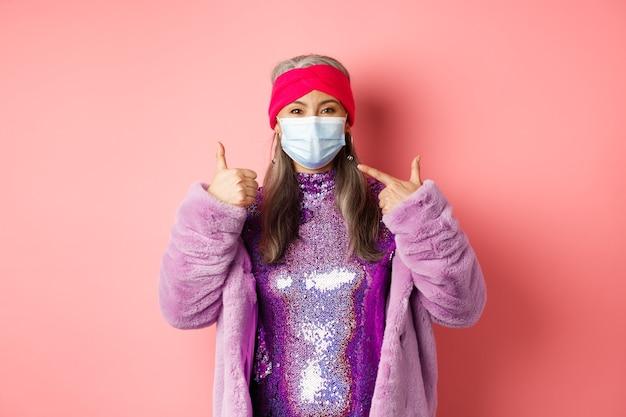 Covid-19、社会的距離とファッションのコンセプト。ファッショナブルな服と呼吸器で笑顔のアジアの年配の女性、フェイスマスクを指して、親指を立てる、ピンクの背景を表示
