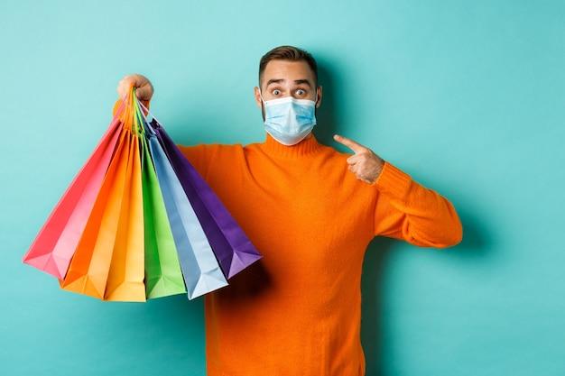 Covid-19, 사회적 거리두기 및 라이프 스타일 개념. 쇼핑 가방을 보여주는 얼굴 마스크에 젊은 남자, 유행성 동안 휴일 선물을 구입, 파란색 배경 위에 서.