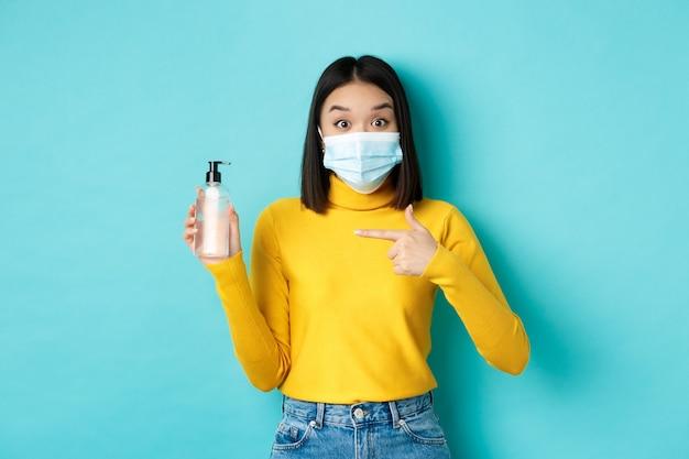 Covid-19, социальное дистанцирование и концепция пандемии. восторженная азиатская женщина в маске для лица, указывая пальцем на дезинфицирующее средство для рук, показывая хороший антисептик, стоя на синем фоне.