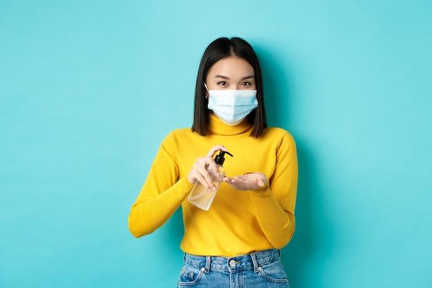 Covid-19, социальное дистанцирование и концепция пандемии. улыбающаяся азиатская женщина в медицинской маске, использующая профилактические меры от коронавируса, используя дезинфицирующее средство для рук, стоя на синем фоне.