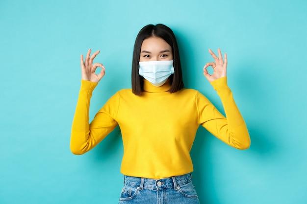 Covid-19, социальное дистанцирование и концепция пандемии. улыбающаяся уверенно азиатская женщина в медицинской маске показывает хорошие знаки, одобряет или хвалит хорошую сделку, стоя на синем фоне.