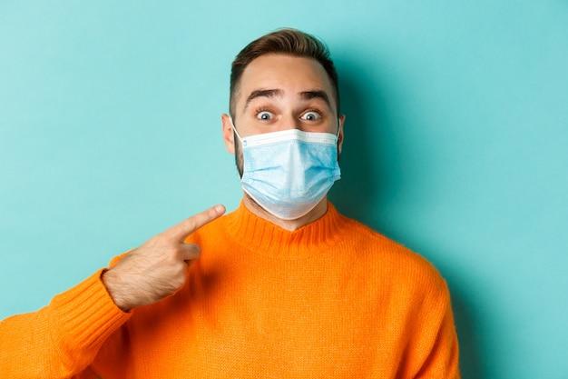 Covid-19, 사회적 거리두기 및 격리 개념. 청록색 배경 위에 서있는 그의 의료 마스크에 쾌활 한 남자 가리키는 손가락의 클로즈업.
