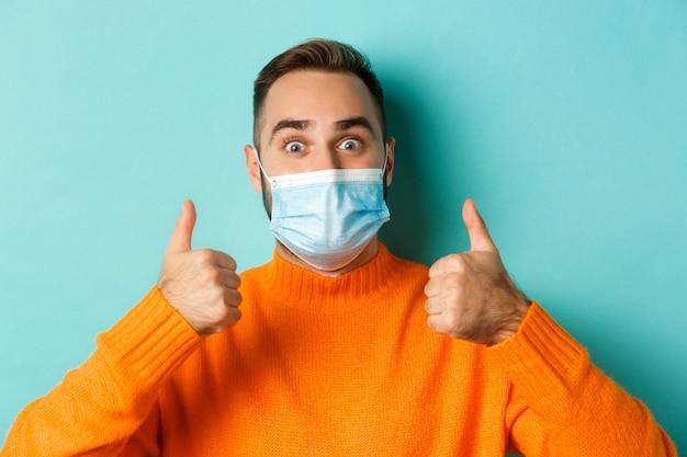 Covid-19、社会的距離と検疫の概念。水色の背景の上に立って、親指を立てて、賞賛し、同意することを示す医療マスクの満足している男性モデルのクローズアップ。