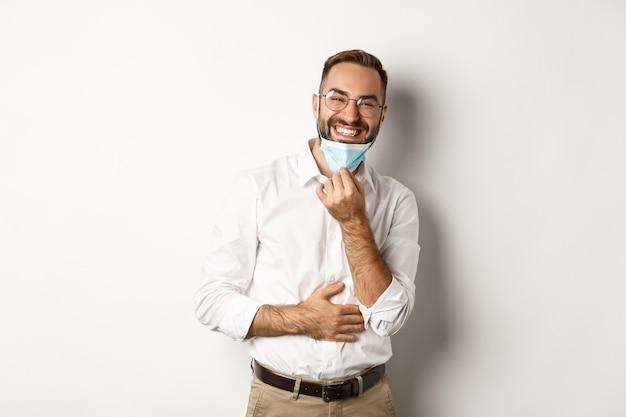 코비드-19, 사회적 거리 및 검역 개념. 행복 한 사업가 얼굴 마스크를 벗고 웃 고, 흰색 배경 위에 서