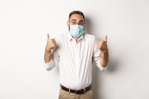 Covid-19、社会的距離と検疫の概念。白い背景に驚いて立って、親指を立てて肩をすくめるフェイスマスクの印象的な男。