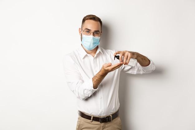 Covid-19, концепция социального дистанцирования и карантина. офисный работник в медицинской маске чистит руки с антисептиком, используя дезинфицирующее средство, стоя на белом фоне.