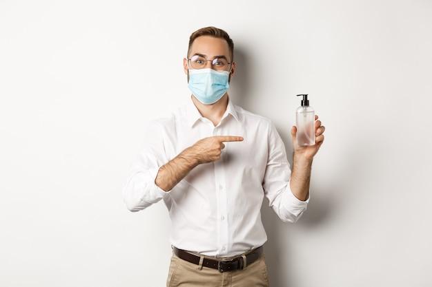 Covid-19, концепция социального дистанцирования и карантина. офисный работник в медицинской маске, указывая на дезинфицирующее средство для рук, показывая антисептик, белый фон.