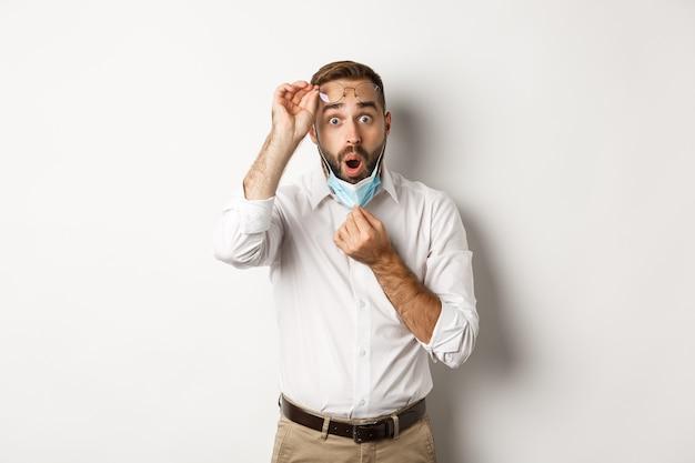 코비드-19, 사회적 거리 및 검역 개념. 놀란 남자는 얼굴 마스크와 안경을 벗고 인상적인 흰색 배경을 보고 있습니다.