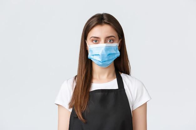 Covid-19の社会的距離、カフェの従業員、コーヒーショップ、コロナウイルスの概念。医療用マスクの女性バリスタのクローズアップ、ウイルス対策のすべてに従い、顧客に食事を提供する
