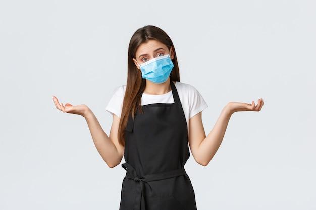 Covid-19社会的距離、カフェの従業員、コーヒーショップ、コロナウイルスのコンセプト。無知なかわいいバリスタ、医療用マスクを着用して肩をすくめて店内にいるレジ係は、気づかず、質問に答えることができません