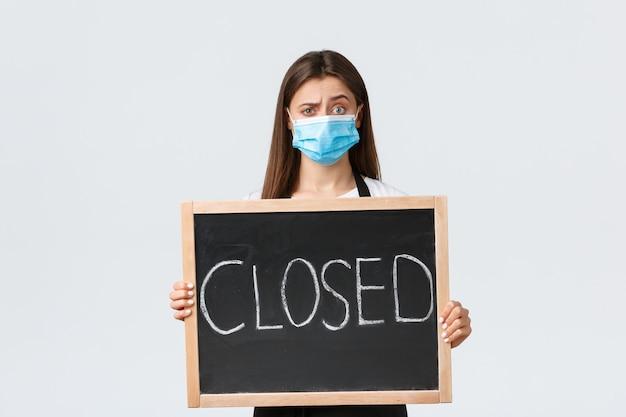 Социальное дистанцирование covid-19, сотрудники кафе, кафе и концепция коронавируса. смущенный и расстроенный бариста в медицинской маске не может понять, почему кафе не может открыться, показывая знак закрыто.