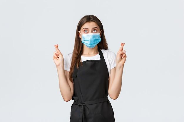 Социальное дистанцирование covid-19, сотрудники кафе, кафе и концепция коронавируса. обнадеживающая милая официантка, кассир или продавщица в черном фартуке и медицинской маске загадывает желание со скрещенными пальцами.